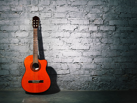 acoustic guitar leaning against a wall