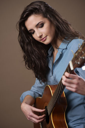 young female guitarist playing an acoustic guitar
